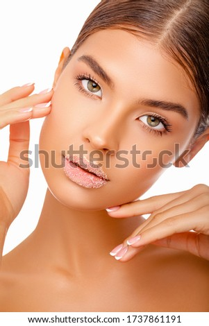 Beautiful Portrait Girl applies Lip Scrub. Lip of Beautiful young Woman covered with Sugar, Closeup.  Female Model Mouth With Smooth Perfect Skin And Natural Manicure Touching Her Plush Lips. Lip Care