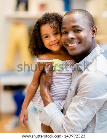 Beautiful portrait of a father and daughter shopping for clothes - stock photo