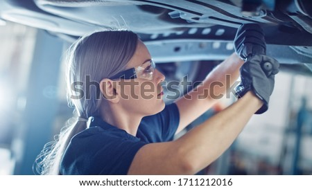 Beautiful Portrait of a Professional Female Car Mechanic is Working Under a Vehicle on a Lift in Service. She is Using a Ratchet. Specialist is Wearing Safety Glasses. Modern Clean Workshop. Photo stock ©