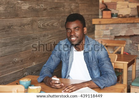 Beautiful portrait of African man sitting in cafe with free wireless connection, drinking fresh coffee with dessert. Satisfied youngster is comfy with morning breakfast and beginning of a new day.