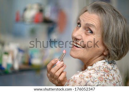 Beautiful portrait of an elder woman making up with lipstick