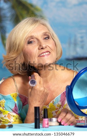 beautiful portrait of an older woman making up