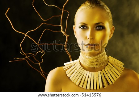 beautiful portrait of attractive blond woman like an amazon with a necklace made of wood peg