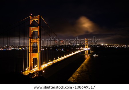 Beautiful  portrait of Golden Gate Bridge at twilight with subtle blue sky and golden hue of the bridge and San Francisco city visible on the far side.