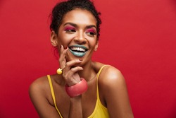 Beautiful portrait of happy african american female model in yellow shirt smiling and posing on camera isolated over red background