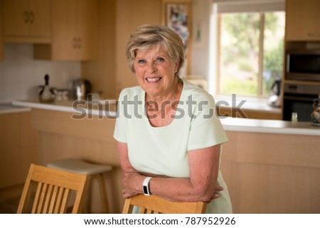 beautiful portrait of pretty and sweet senior mature woman in middle age around 70 years old smiling happy and friendly at home kitchen in aging and lifestyle concept, #787952926
