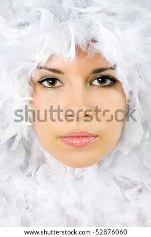 Beautiful portrait of young woman surrounded by feathers