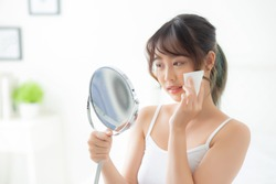 Beautiful portrait young asian woman smile with skin care use oil blotting paper on face looking mirror at room, beauty asia girl happy and cheer makeup and cosmetic, health care on facial concept.