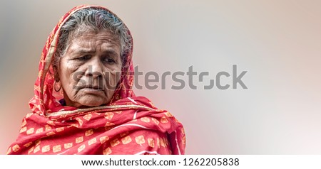 Beautiful pose of an elderly woman of Indian Origin, having wrinkles on her face and white & grey hair, wearing red saree with veil, thinking in sorrow. Plane background space for taglines/advertising