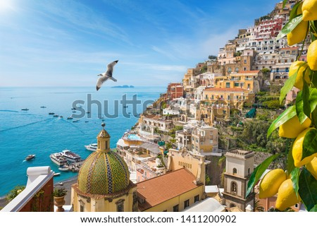 Beautiful Positano with comfortable beaches and clear blue sea on Amalfi Coast in Campania, Italy. Amalfi coast is popular travel and holyday destination in Europe. Ripe yellow lemons in foreground.