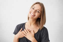 Beautiful positive friendly-looking young mixed race woman with lovely sincere smile feeling thankful and grateful, showing her heart filled with love and gratitude holding hands on her breast