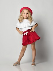 Beautiful positive little blonde girl with curly hair in stylish casual clothing, sandals and hat standing and smiling over grey wall background. Fashion for children concept