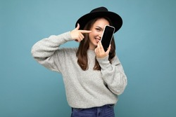 Beautiful positive woman wearing black hat and grey sweater holding mobilephone showing smartphone isolated on background looking at camera