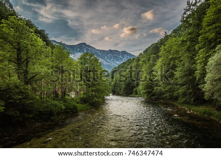 beautiful postcard view of mountain river with forest banks against cloudy blue sky background #746347474