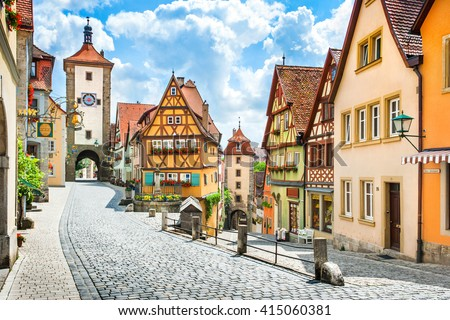 Beautiful postcard view of the famous historic town of Rothenburg ob der Tauber on a sunny day with blue sky and clouds in summer, Franconia, Bavaria, Germany #415060381