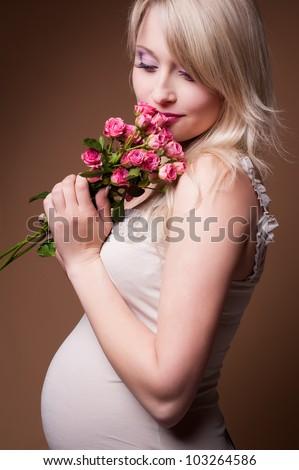 Beautiful pregnant blond woman , a studio portrait.