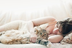 Beautiful pregnant girl sleeping on a bed with a beautiful large cat