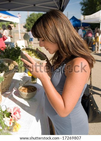 Beautiful pregnant Hispanic woman sniffing dried chamomile at the Farmers' Market.