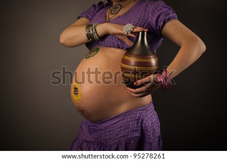 Beautiful pregnant middle aged woman with painted on the body chakras, holding jug