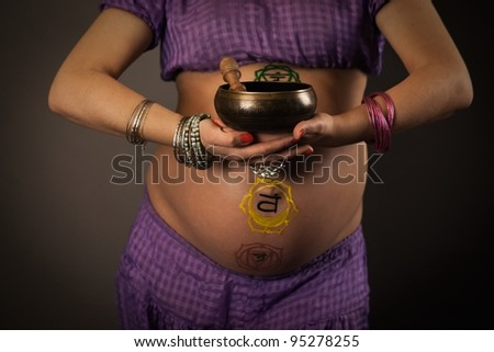 Beautiful pregnant middle aged woman with painted on the body chakras, holding singing bowl