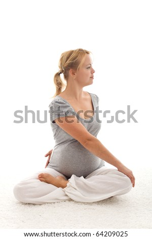 Beautiful pregnant woman doing exercises sitting on the floor - isolated - stock photo