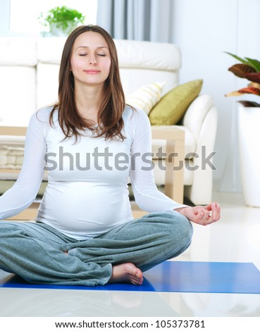 Beautiful Pregnant Woman Doing Yoga at Home. Relaxation
