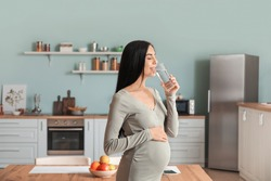 Beautiful pregnant woman drinking water in kitchen