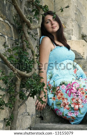 beautiful pregnant woman in blue clothes near the house