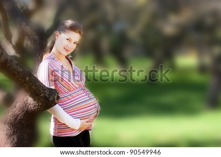 Beautiful pregnant woman in park