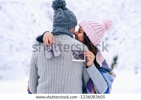 600e0e7a2aef2 Beautiful pregnant woman in warm pink hat holds ultrasonic pregnant picture and  baby shoes in her