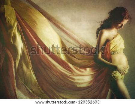 Beautiful pregnant woman  in waving fabric - stock photo