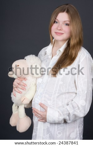beautiful pregnant woman in white holding toy on grey background