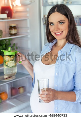 Beautiful pregnant woman is holding a jug of lemonade and a glass, looking at camera and smiling while standing near the open fridge in her kitchen at home