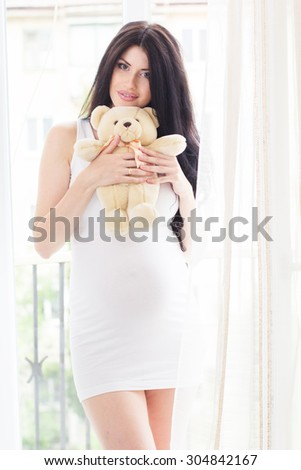 Beautiful pregnant woman is holding and hugging toy teddy bear