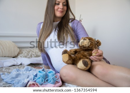Beautiful pregnant woman laying in her bed with Teddy Bear in her arms