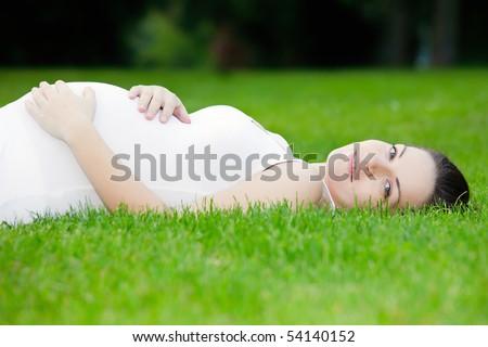 Beautiful pregnant woman laying on grass