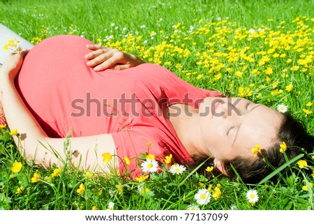 Beautiful pregnant woman laying on grass
