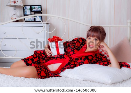 beautiful pregnant woman on a bed with a gift