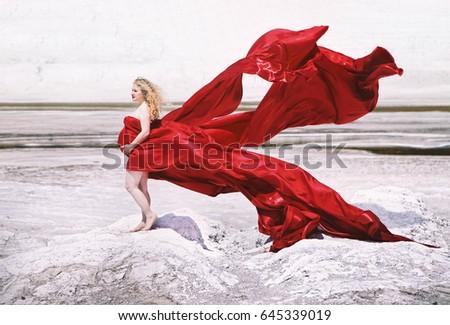 Beautiful pregnant woman outdoors, red dress like flower - Shutterstock ID 645339019