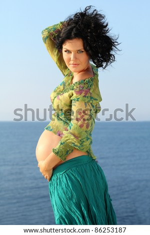 Beautiful pregnant woman over sky background, outdoors