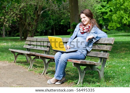 Beautiful pregnant woman sitting on bench