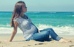 beautiful pregnant woman sitting on the beach