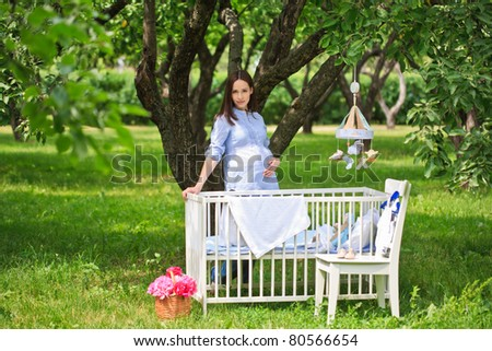 Beautiful Pregnant woman standing by cradle in a garden