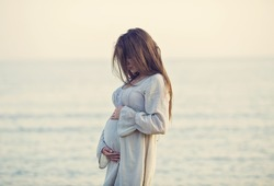 beautiful pregnant woman standing on the beach