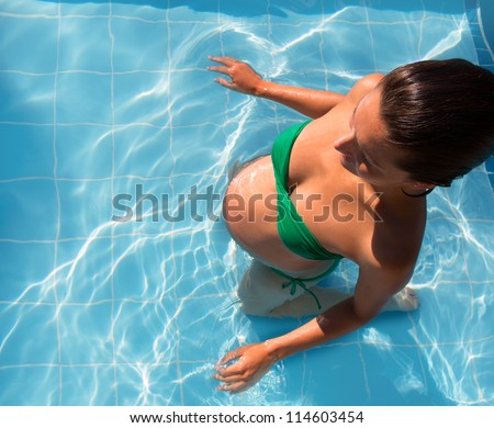Beautiful pregnant woman sun tanning relaxed at blue pool with green bikini