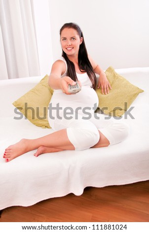 Beautiful pregnant woman watching TV on sofa at home
