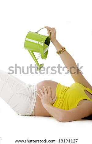 Beautiful pregnant woman watering her tummy to make the Baby growing