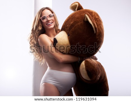 Beautiful pregnant woman with bear