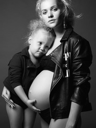 beautiful pregnant woman with child. beauty stylish Mother and daughter. Happy Family. young mother woman with child baby girl