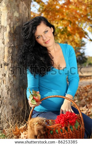 Beautiful pregnant woman with foodstuffs, autumn outdoors
